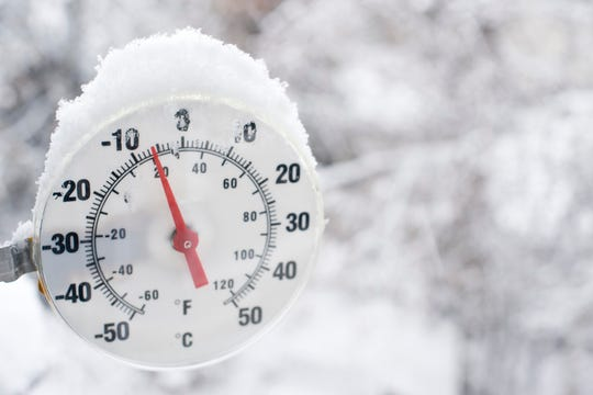 A thermometer showing freezing temperatures and falling snow