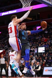 Mavs guard Jalen Brunson shoots around Pistons forward Blake Griffin on Thursday.