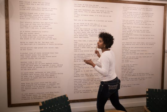 Kela Harris of Detroit reads over a poem on a wall while looking for clues.