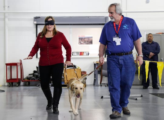 Ginger Auten, Human Resources manager and administration, left, walks blindfolded with Coco and trainer Mike Toger during a Harness the Power of Leadership session at Mitsubishi Motors R&D Of America Ann Arbor Laboratory, Tuesday, Jan. 29, 2019.