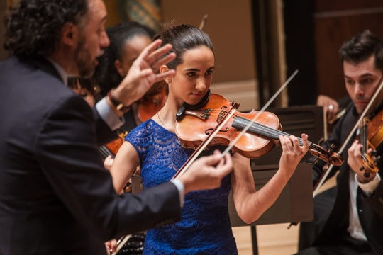 Sophia Ayer, 16, of Austin, TX plays the violin as guest conductor Carlos Andres Botero (left) leads the Sphinx Honors Orchestra while competing in the Junior Division Honors Concert of the 22nd Annual Sphinx competition.
