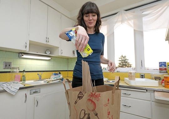 Bethany empties pasta into a food composting bag.