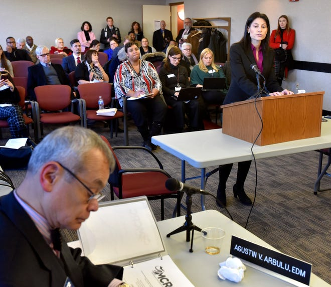Michigan Attorney General Dana Nessel, right,  addresses Michigan Civil Rights commissioners as Dr. Agustin V. Arbulu, left, director of the Michigan Department of Civil Rights, takes notes.