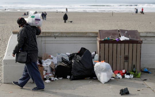 In this Jan. 3, 2019, file photo, a woman walks past trash piled next to a garbage bin at Ocean Beach in San Francisco.