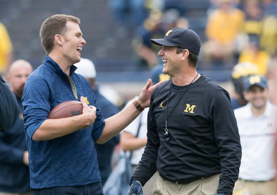 Tom Brady and Jim Harbaugh talk on the Michigan Stadium field during warmups before the Wolverines' game against Colorado in 2016.
