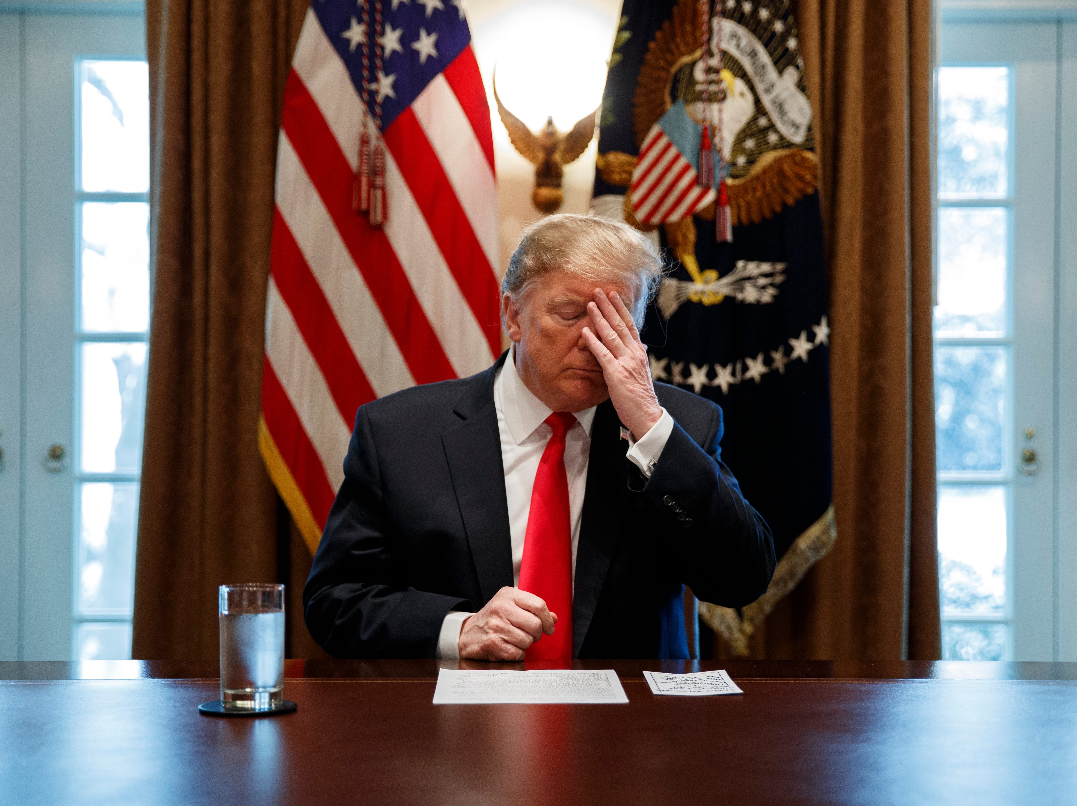 President Donald Trump adjusts his eyebrows before speaking during an event on human trafficking in the Cabinet Room of the White House, Friday, Feb. 1, 2019, in Washington.