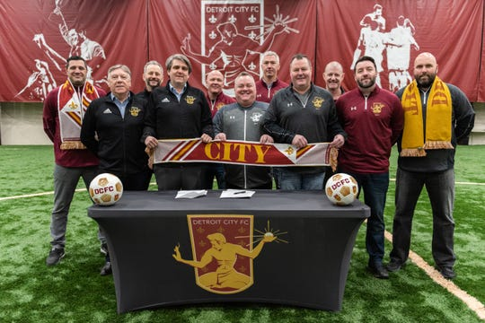 Sam Piraine, Canton Soccer Club technical director, from left; joins Trevor James, Detroit City Football Club coach; Alex Wright, DCFC co-owner; Sean Mann, co-owner; Rob Nuckolls, Genesee Celtic president/club director; Jim Harkins, Canton Soccer Club president; Dan McEvilly, Canton Soccer Club manager; Pete Alexander, Canton Soccer Club director; Steve Applebee, Genesee Celtic board member; Charlie Bell, Canton Soccer Club girls director of coaching; and Ian Jones, Canton Soccer Club boys director of coaching; join in the signing agreement at Detroit City Fieldhouse.