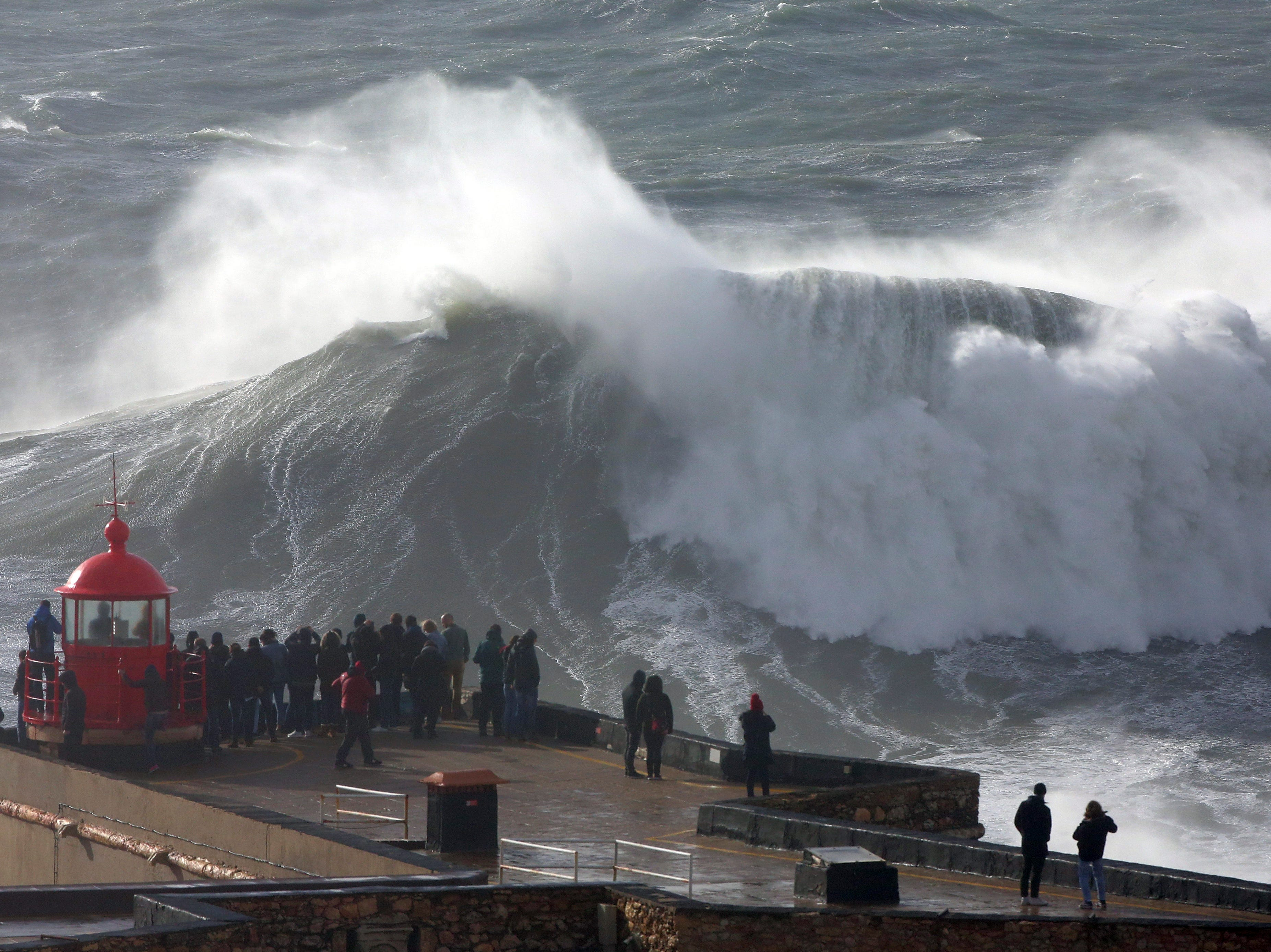 People gather on the roof of the Nazare lighthouse to watch big waves crashing at the Praia do Norte, or North Beach, in Nazare, in Portugal's west coast, Friday, Feb. 1, 2019. Waves over 10 meters high and strong winds were forecast to hit the Portuguese coast on Friday.