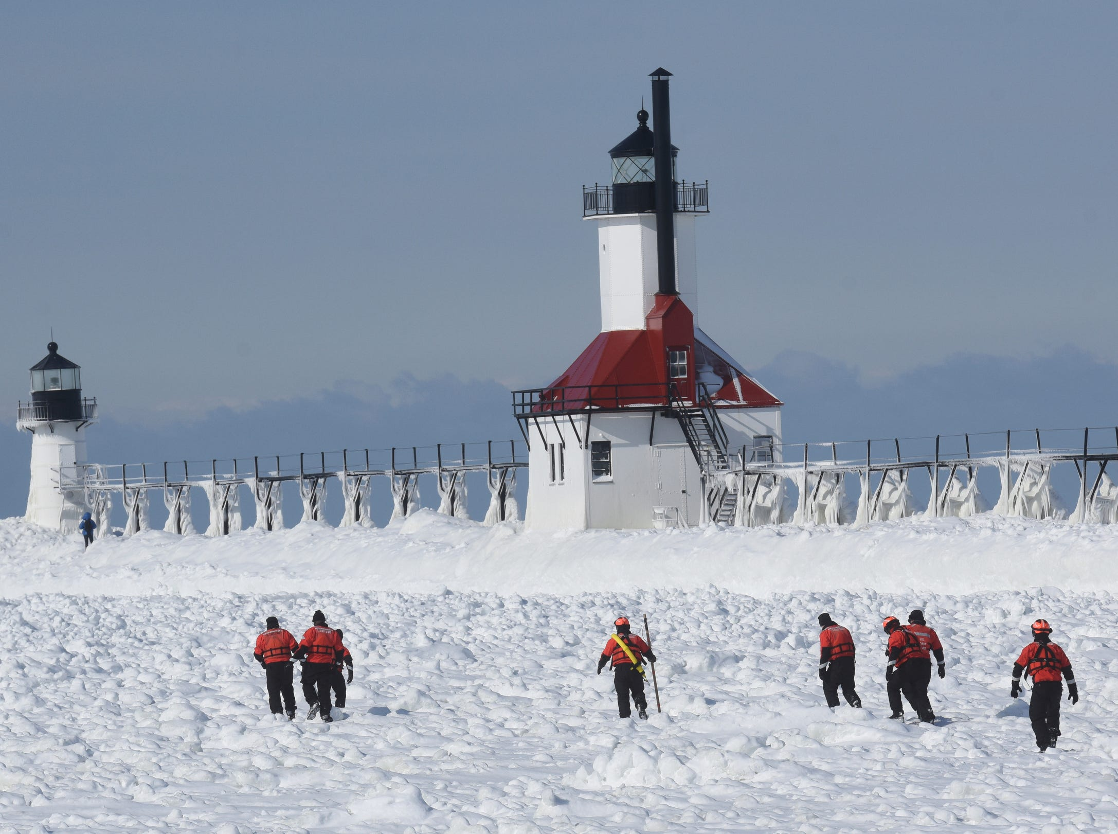 Members of the U.S. Coast Guard Station, in St. Joseph, Mich., cross the frozen St. Joseph River channel as they take part in ice rescue techniques near Lake Michigan and the St. Joseph Lighthouses Friday, Feb. 1, 2019.