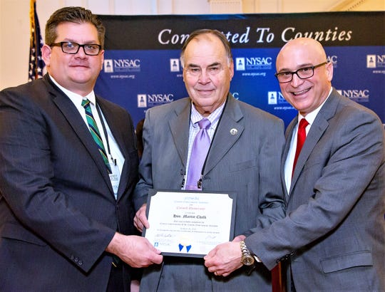 Chemung County legislator Marty Chalk, center, accepts a certificate from New York State Association of Counties President Charles H. Nesbitt Jr., left, and NYSAC Executive Director Stephen J. Acquario.