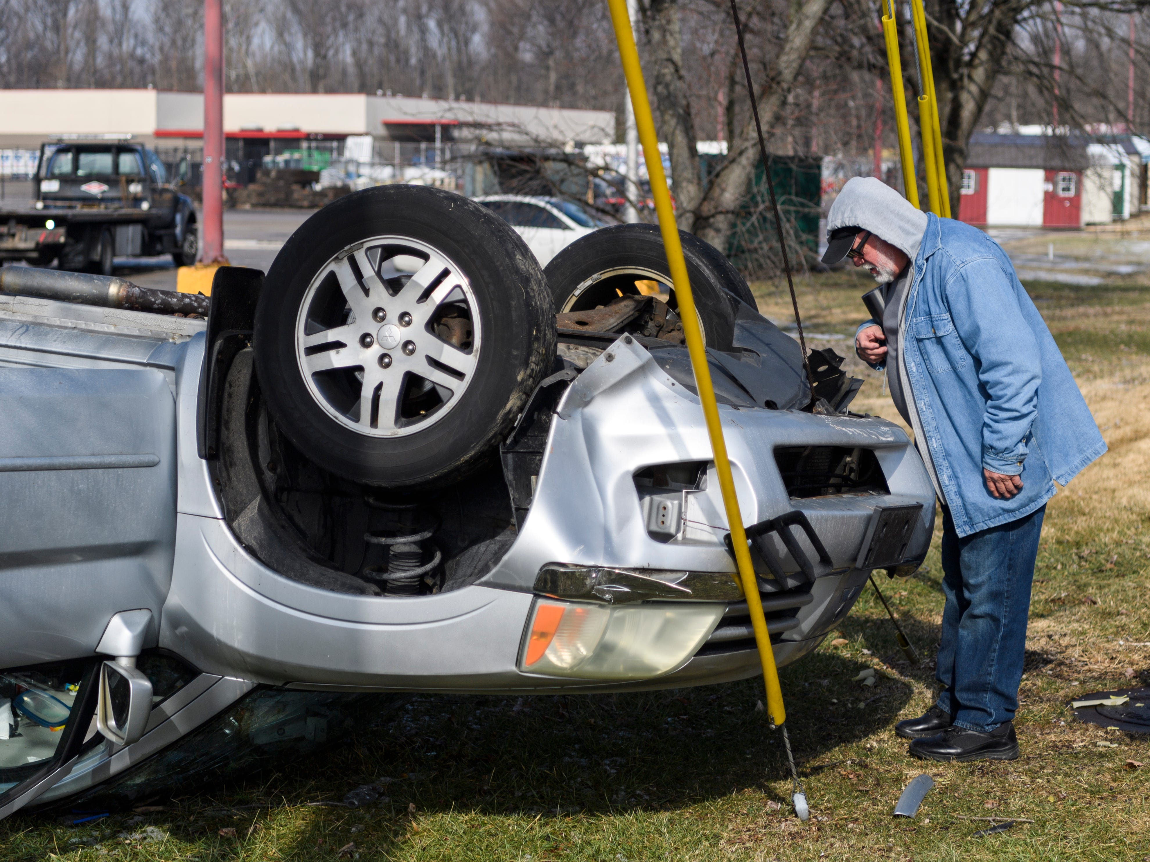 Donnie Bowers takes a closer look at the car he watched flip over in a single-vehicle accident near the intersection of Boeke Road and Morgan Avenue in Evansville, Ind., Friday, Feb. 1, 2019. Bowers and his friend Bill Belwood, not pictured, were talking in the parking lot of Hardee's, across the street, when he saw the vehicle flip over and quickly called 911.