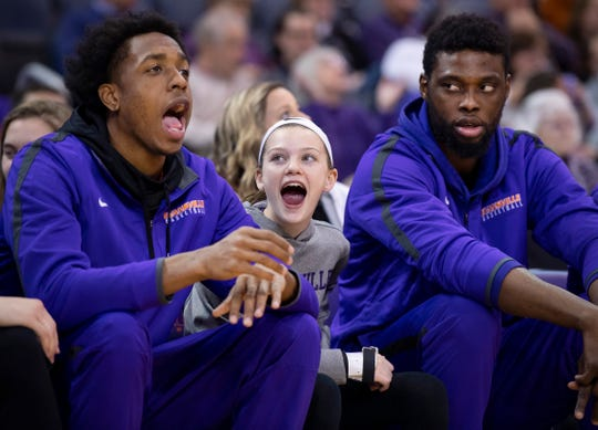 Lillian Graves, 11, sits on the end of the Purple Aces' bench with redshirt players Deandre Williams, left, and Peace Ilegomah during their game against Bradley University at the Ford Center Wednesday night. Graves is the daughter of Matthew Graves, an assistant coach with the team. Head Coach Walter McCarty is a proponent of coaches' kids spending time around the basketball operation since family time is in short supply during the season.
