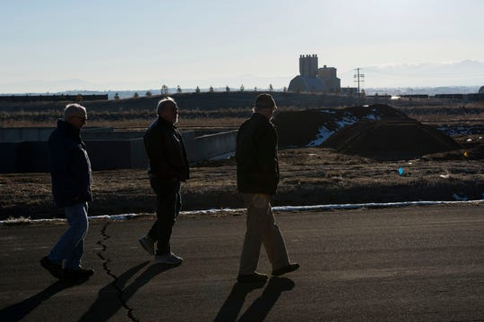Indianhead Estates subdivision residents, from left, Gary Oplinger, Jim Piraino and Wolfgang Dirks, walk along the west side of the neighborhood while the former Martin Marietta Materials distribution center, now owned by Rock & Rail LLC, stands in the distance.
