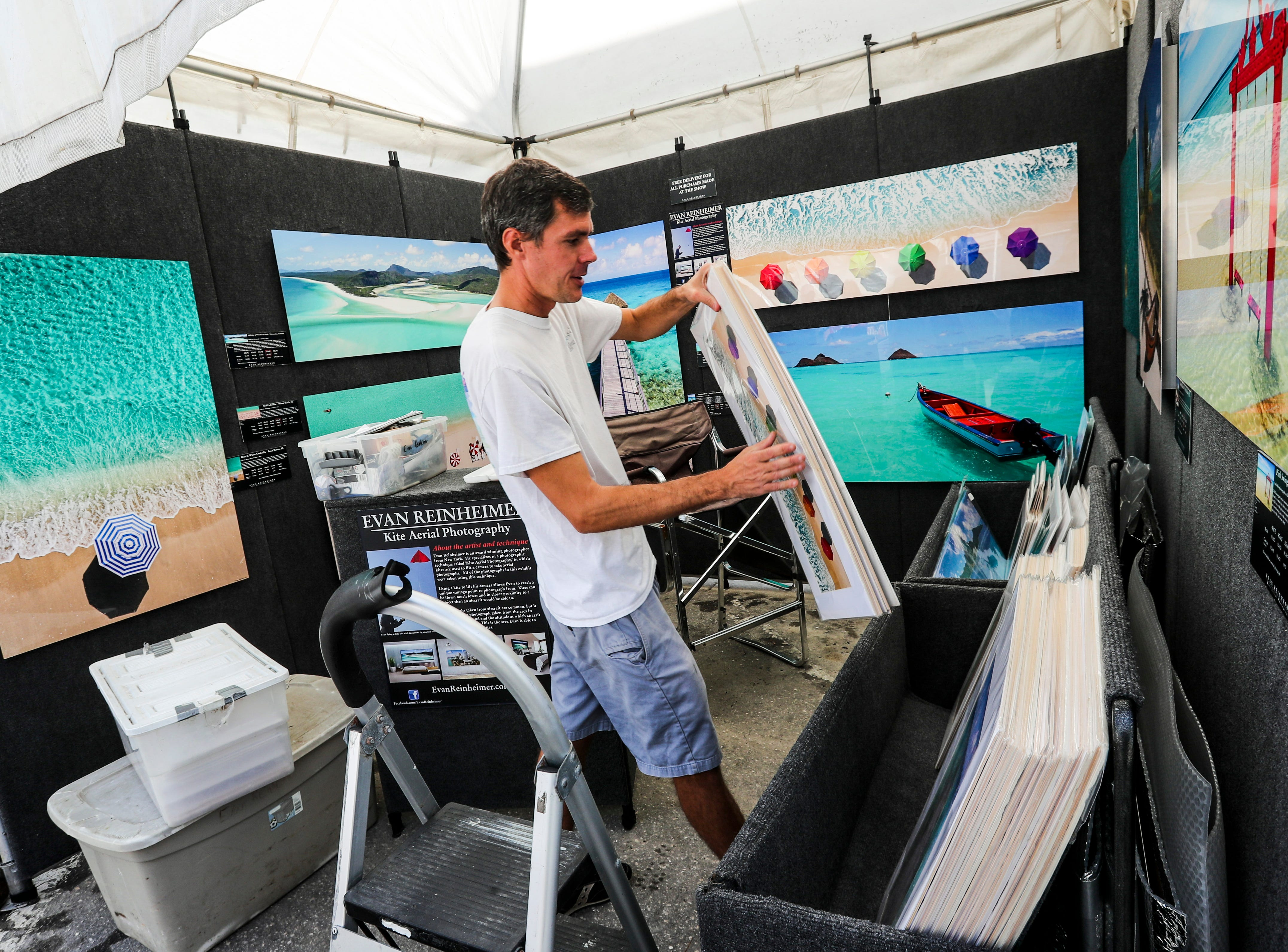 """Evan Reinheimer , of New York, specializes in """"Kite Aerial Photography"""". He sets up his booth Friday morning. Artists spent the morning setting up for ArtFest Fort Myers downtown on Edwards Drive. The festival goes all weekend."""
