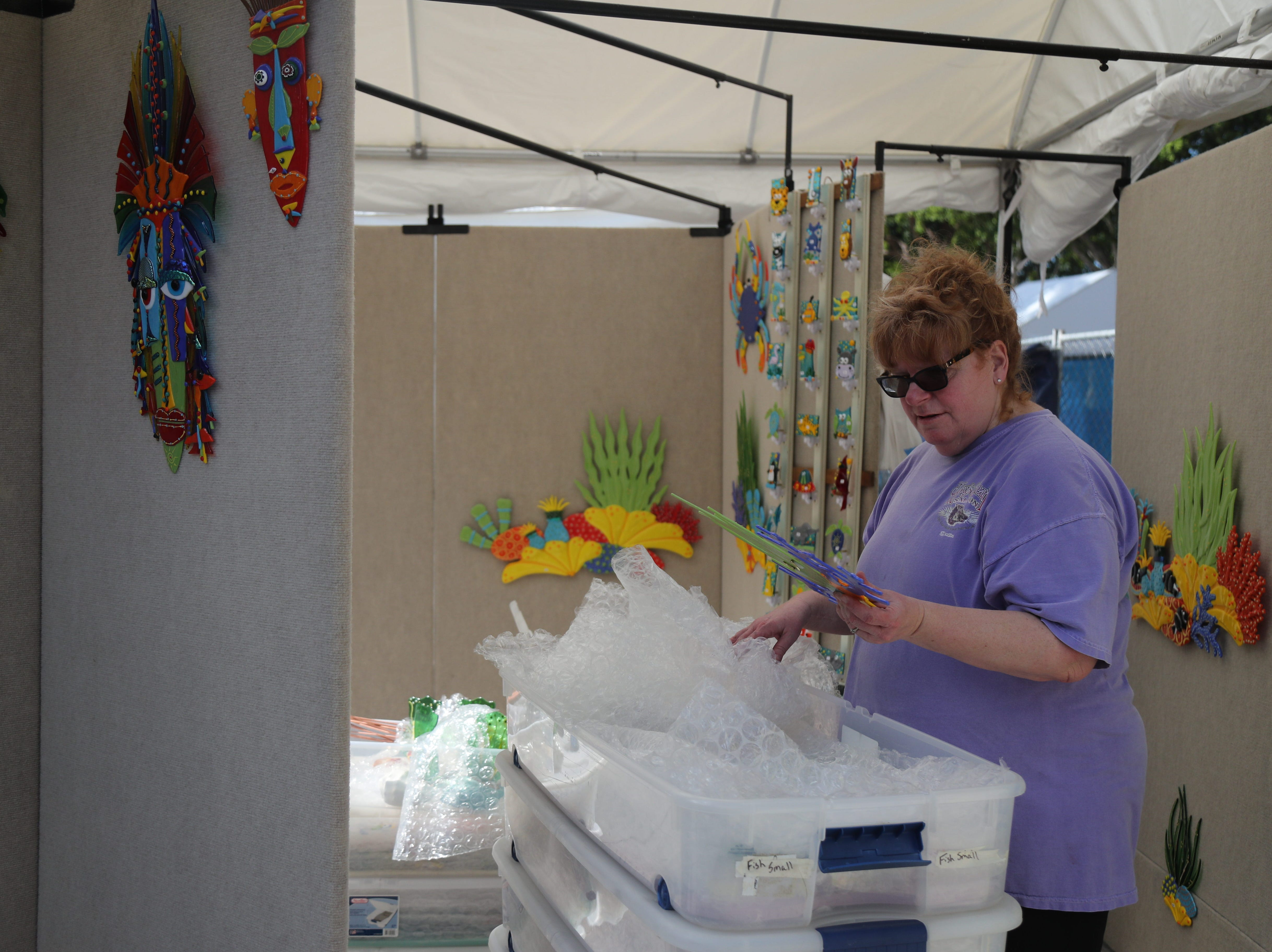 Charlene Heilman, a glass artist from Lily, Kentucky, sets up at ArtFest in downtown Fort Myers on Friday, Feb 1, 2019.