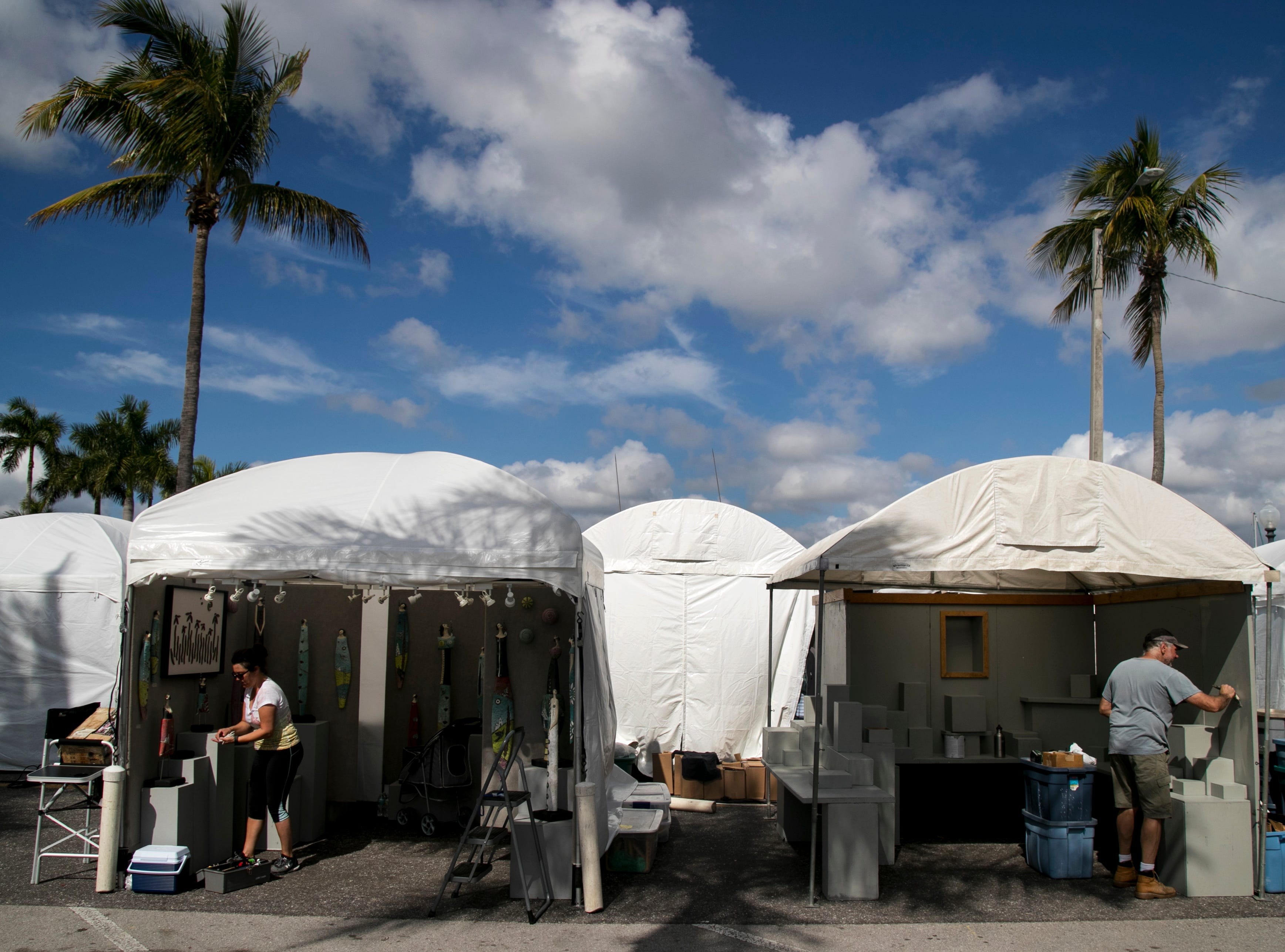 Clay artist Tanya Tyree of Baltimore, left, sets up her tent Friday afternoon, Feb. 1, 2019, while preparing for ArtFest in downtown Fort Myers. More than 200 artists will have their art on display at ArtFest, which is open Saturday and Sunday from 10 am to 5 pm.