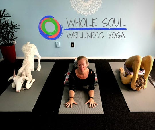 Jaime Boswell of Whole Soul Wellness Yoga poses with two of 3-D artist Jeff Abbott's creations. Abbott is a Pine Island resident.