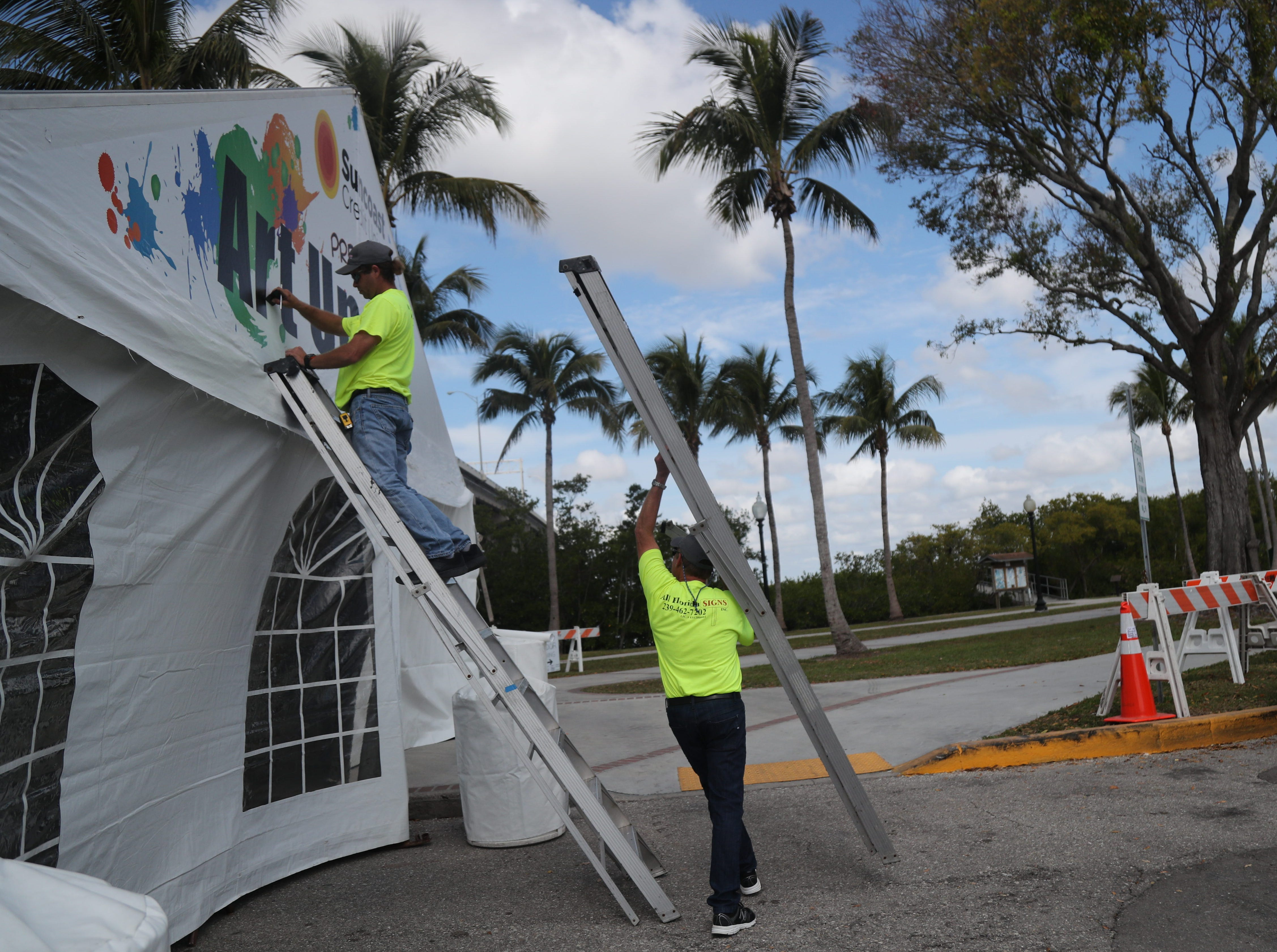 Ryan Freeman, left, and Leroy Leonov add the sign to the Art Under 20 tent at ArtFest in downtown Fort Myers on Friday, Feb 1, 2019.