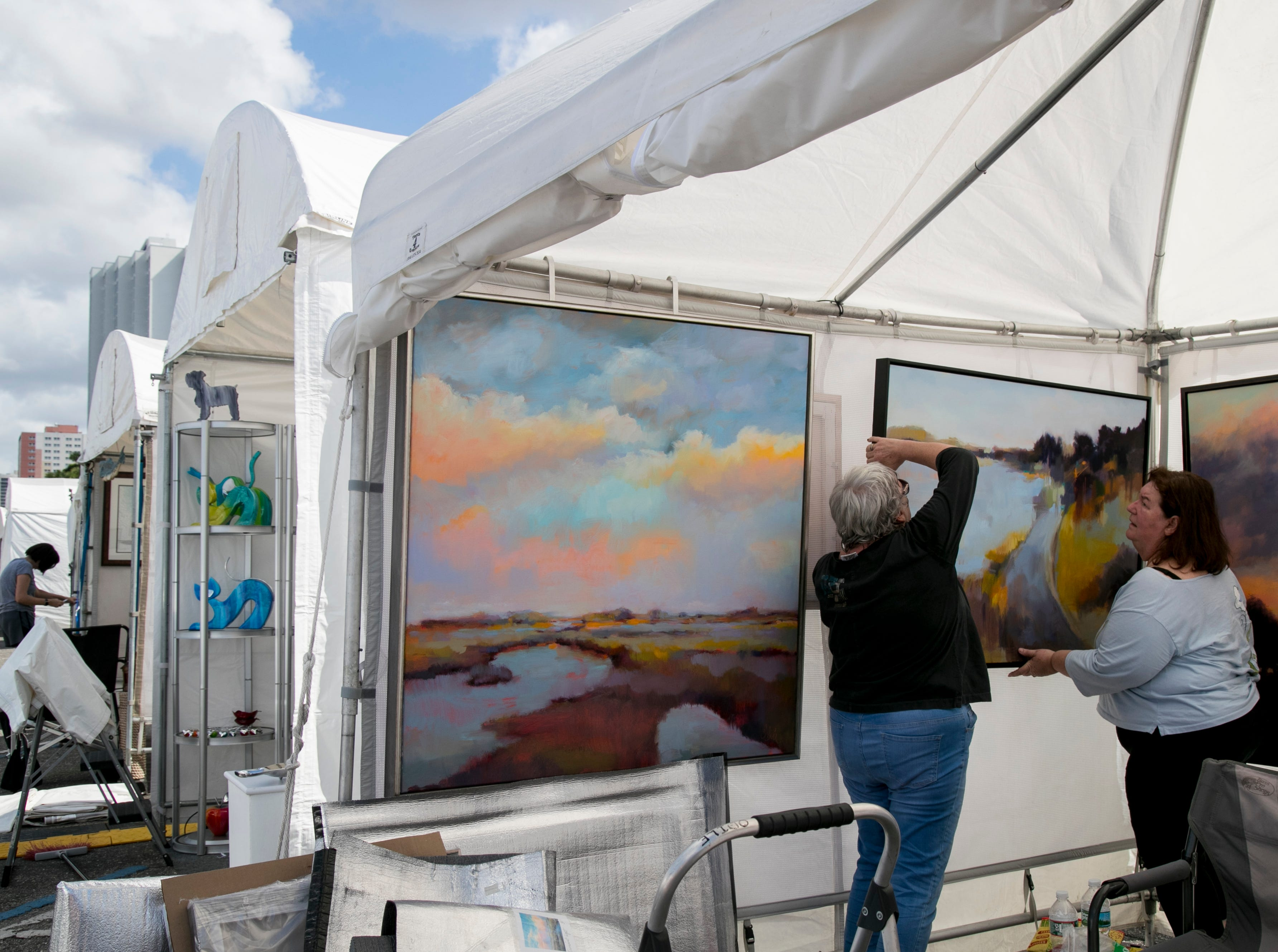 Claire Kimball, left, and artist Ruth Davis, right, of Harwich, Mass., hang a painting while setting up for ArtFest in downtown Fort Myers on Friday, Feb. 1, 2019. ArtFest is open Saturday and Sunday from 10 am to 5 pm.