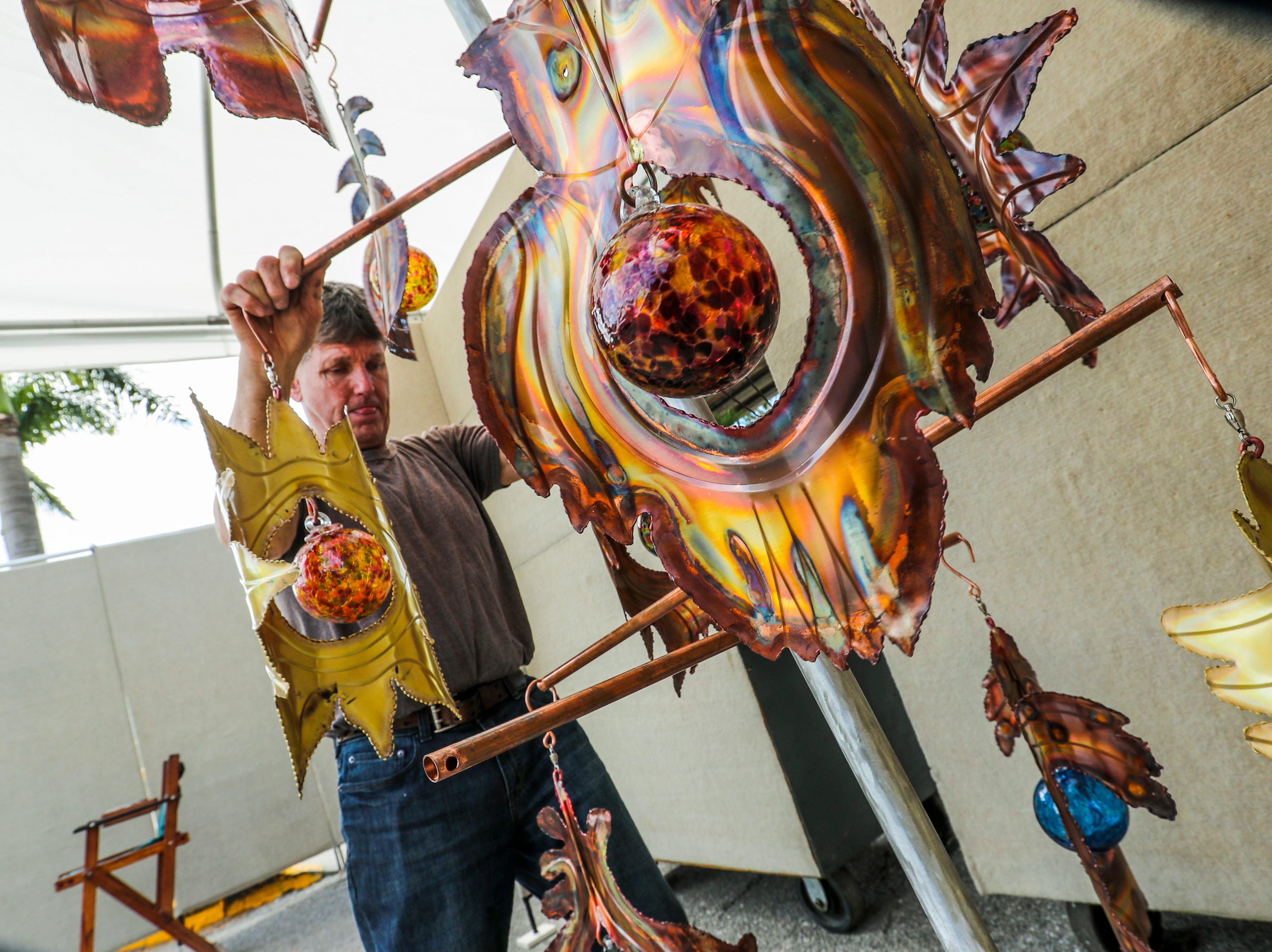 Steve Anderson, Anderson's Metal Sculpture, out of Cedar Springs, MI, moves around his art as he sets his booth up Friday morning. His boothArtists spent the morning setting up for ArtFest Fort Myers downtown on Edwards Drive. The festival goes all weekend.