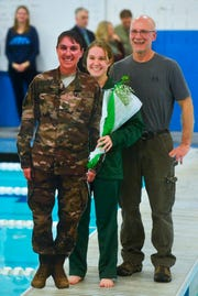 CMR senior Darlene Westie poses for a photo with her father Kevin and a life size cutout of her mother Amber, who is deployed overseas with the U.S. Air Force, during the senior night ceremony at the crosstown swim meet, Thursday evening.