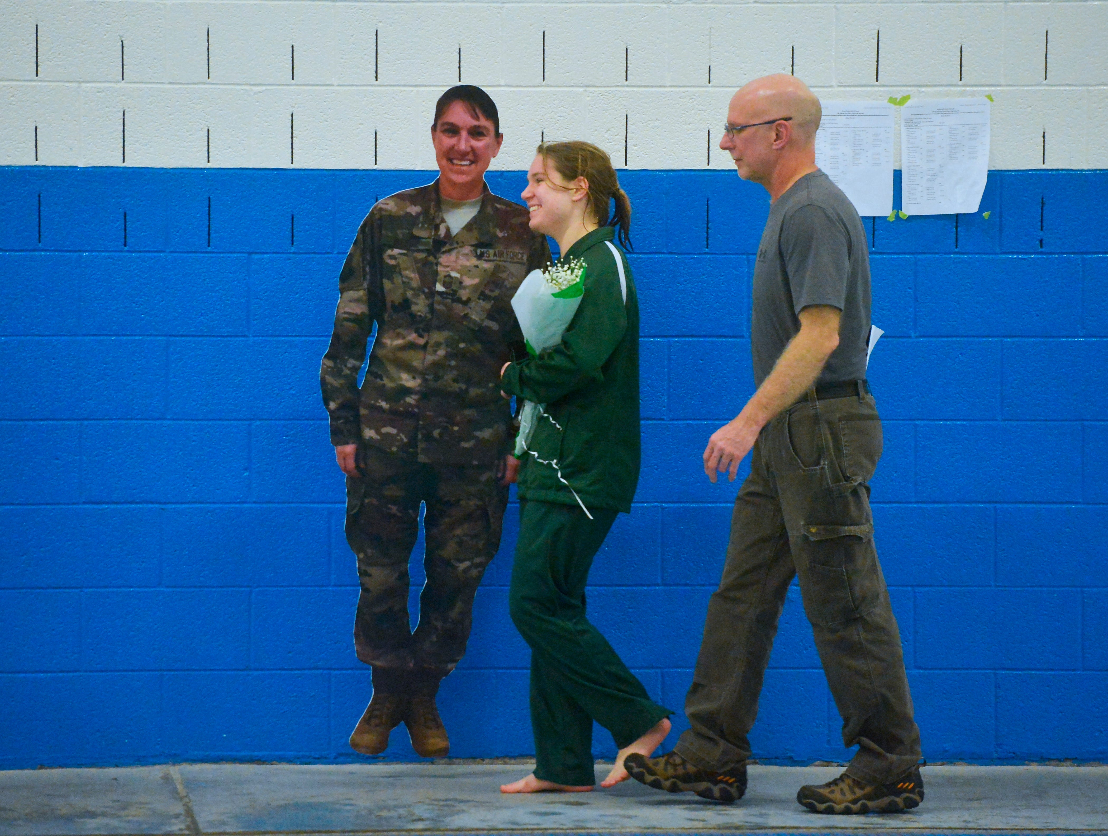 CMR senior swimmer Darlene Westie walks with her father Kevin and a life size cutout of her mother Amber, who is deployed overseas with the U.S. Air Force, during the senior night ceremony at the crosstown swim meet, Thursday evening.