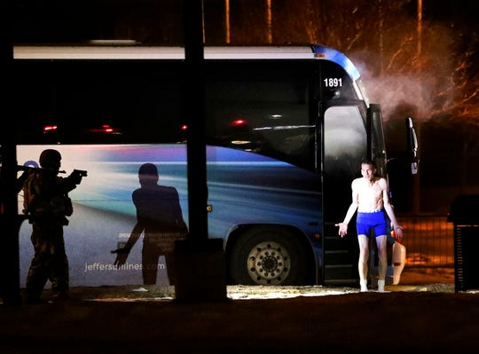 Police arrest suspect after he exited the bus and removed his clothing on Wednesday, Jan. 30, 2019,  near at the bus transfer station near the Butte Civic Center in Butte, Mont.  The bus was heading from Missoula to Billings when the man put a gun to the driver's head and said he wanted to go to the Butte courthouse. The driver stopped to the Butte Civic Center instead. The hijacker, who is believed to have had an explosive device in addition to the gun, allowed the driver and passengers to get off, except for one passenger he held as a hostage. (Meagan Thompson/The Montana Standard via AP)
