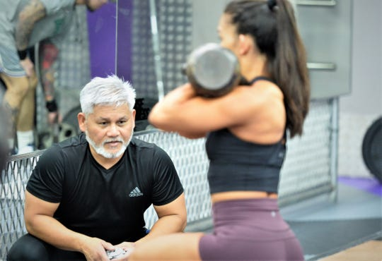 Personal fitness trainer Steve Oshiro looks for proper form from one of his winning clients, Jeralyn Mesa, during a workout at Paradise Fitness Center in Hagåtña in November 2018.