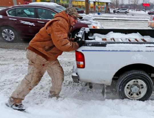 Amin Contreras stops to help another driver unstuck, to turn from 86th St. onto Michigan, Friday, Feb. 1, 2019,  Bumper to bumper traffic crawled westward on 86th St. as drivers navigated the snowy roads.  Some cars, like this one, got stuck on unplowed turn lanes.