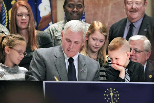 Children of Indiana National Guard Sgt. Jeremy Barts and his wife Jamie, Elkhart, watch as Indiana Gov. Mike Pence signs SEA 352 into law, giving more military families access to the Military Family Relief Fund. Sen. Allen Paul, bottom right, carried the bill. The ceremony was held at the Indiana War Memorial in Indianapolis on Thursday, March 13, 2014.