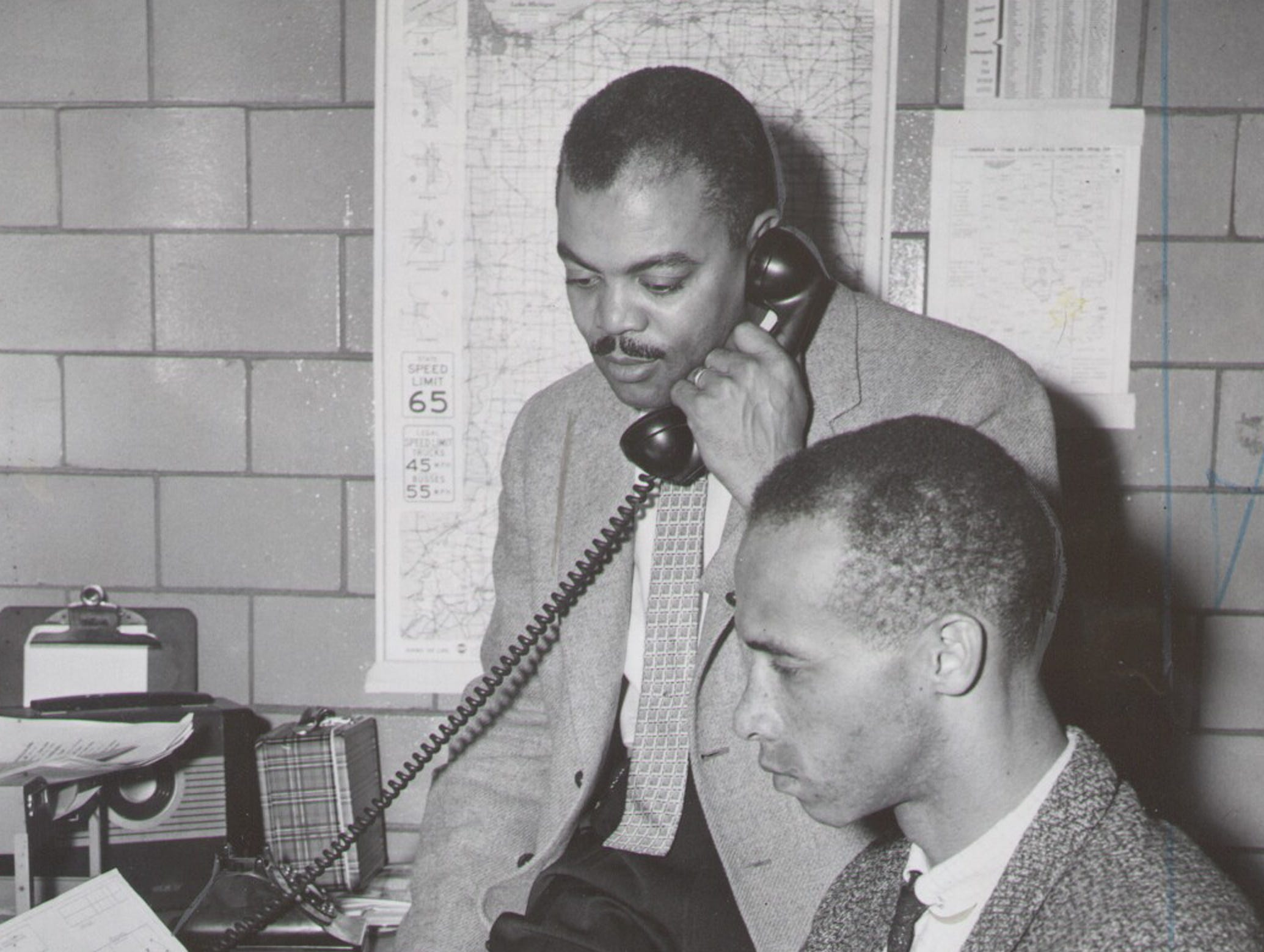 Attucks coach Bill Garrett (front) looks over scouting reports on the Madison Cubs, the opponent in the 1959 semistate tournament, while Ray Crowe, Athletic Director Ray Crowe answers the phone.  March 11, 1959