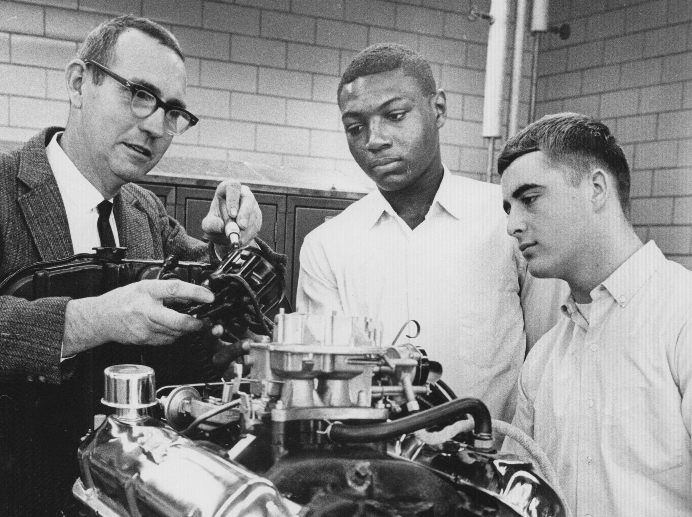 Washington High School students Bill Rogers and John Hill watch as auto shop instructor Stewart Joyce works on a Ford 289 cubic inch, V-8 engine donated in 1966 by the Ford Motor Co. due to a demand for trained auto mechanics.