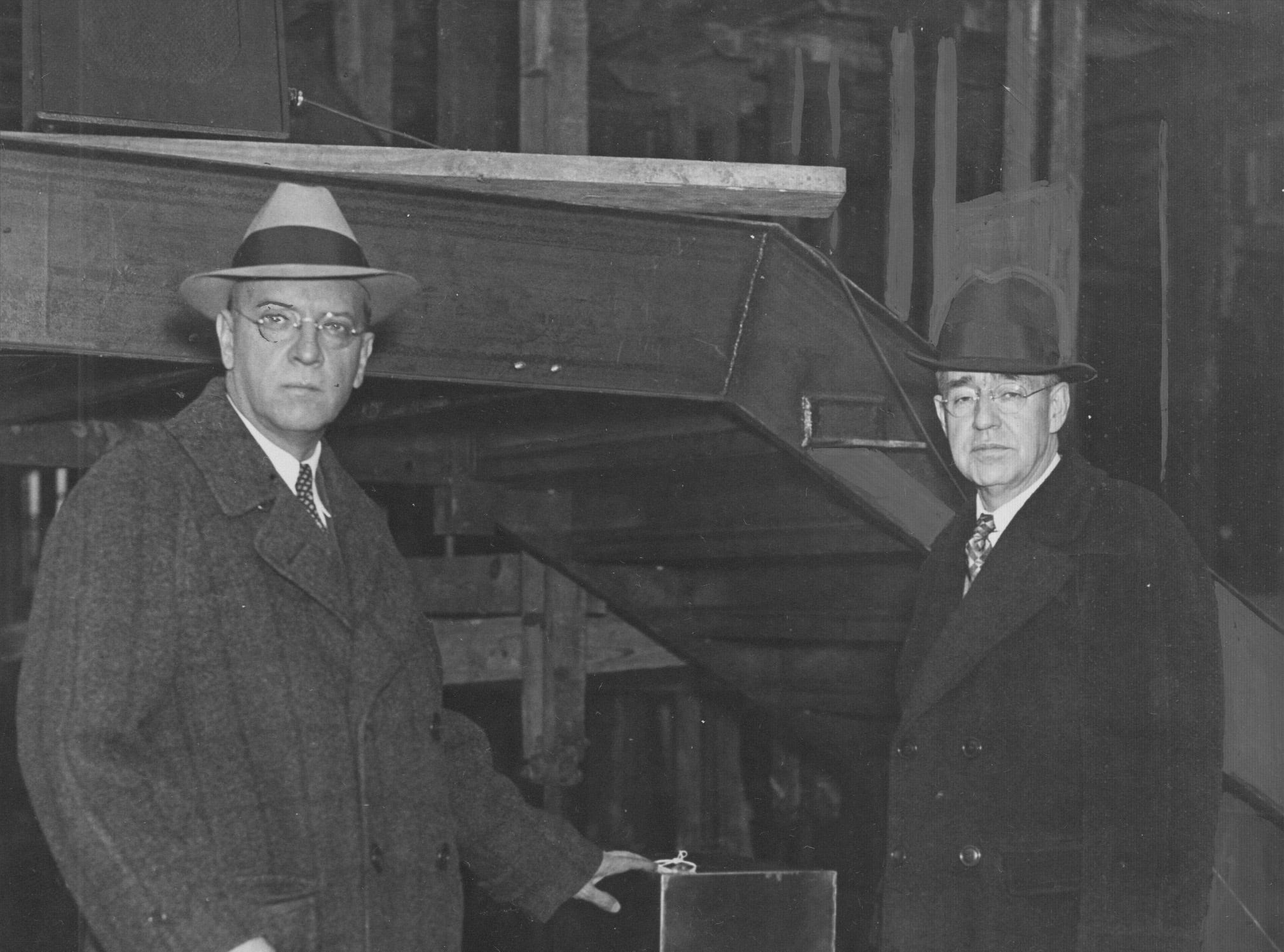Carl Wilde, vice-president of the Board of School Commissioners (left), is shown laying the cornerstone to the addition at George Washington High School as Walter Gingery, school principal assisted.