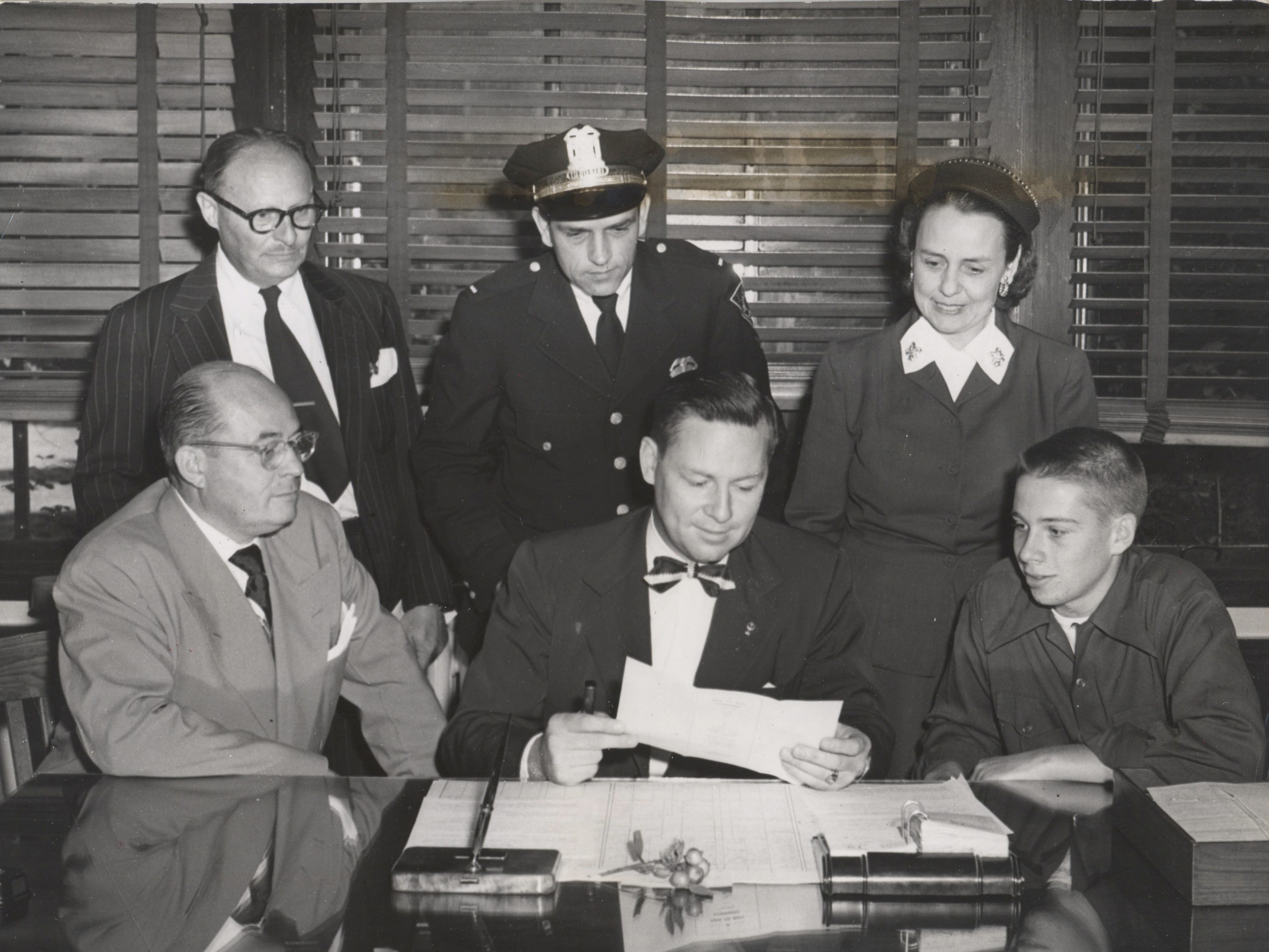 "Judge Alex M. Clark of the Indianapolis Municipal Court reads the terms of the ""Man to Man"" teenagers driving agreement to Donald R. Morris, 17 year-old Shortridge High School senior, this being preliminary to the launching of a safe driving campaign for the youths of Indianapolis in Caleb Mills Hall at Shortridge High School in 1949. In the picture seated are Ralph D. Morris, left, father of Donald Morris, right. Judge Clark is in the middle Standing left to right are Thomas E. Hanika, manage of the Indianapolis Automoblie Trade Association; Lieut. Harry Bailey of the Traffic Safety Education Division, Indianapolis Police and Mrs. M. Lugar, president of the Shortridge Parent Teacher Association."
