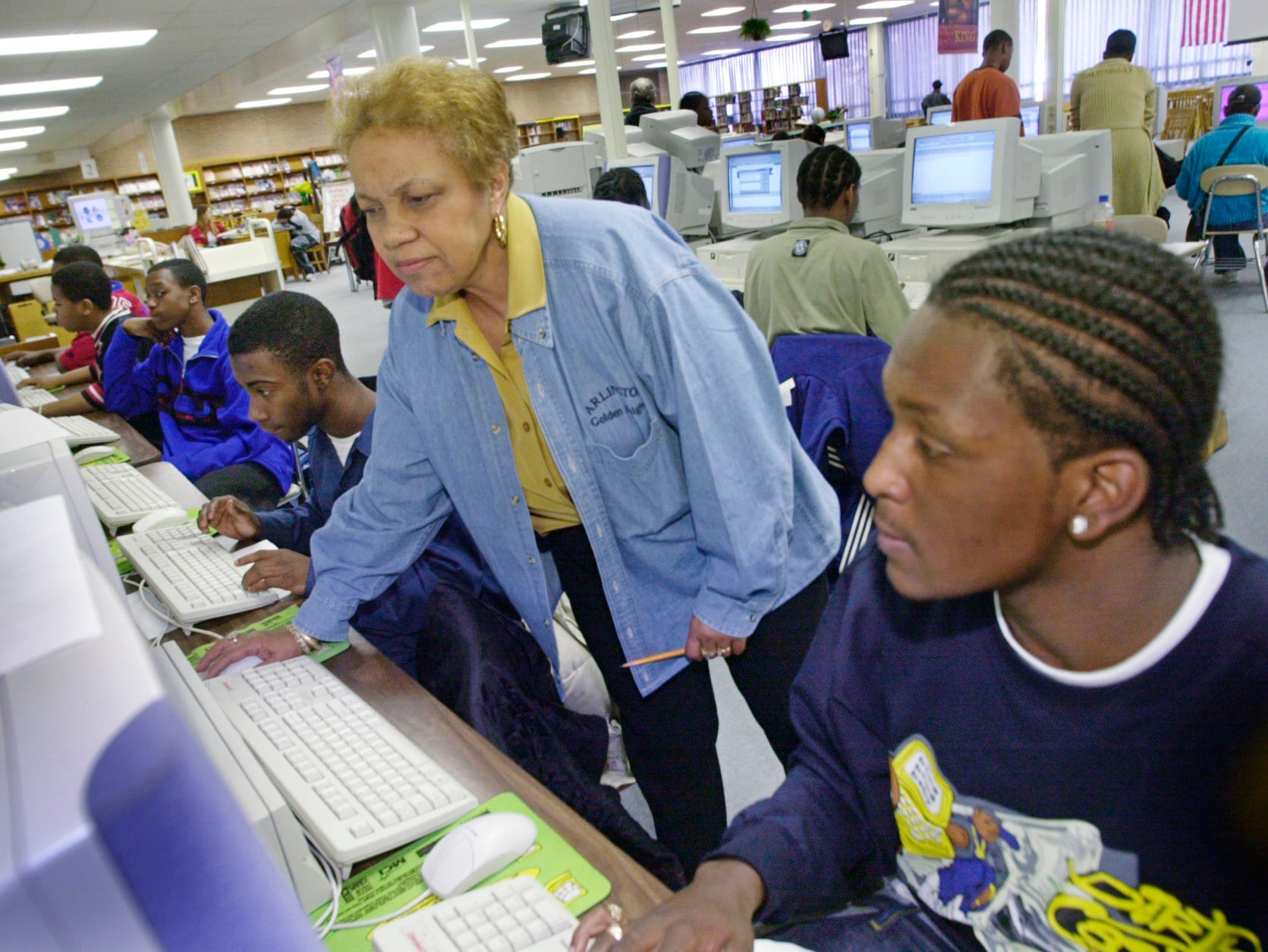 Shirley Lynch (standing) helps student Renaldo Logan (with an exercise on the computer in the Arlington High School Media Center in 2002..