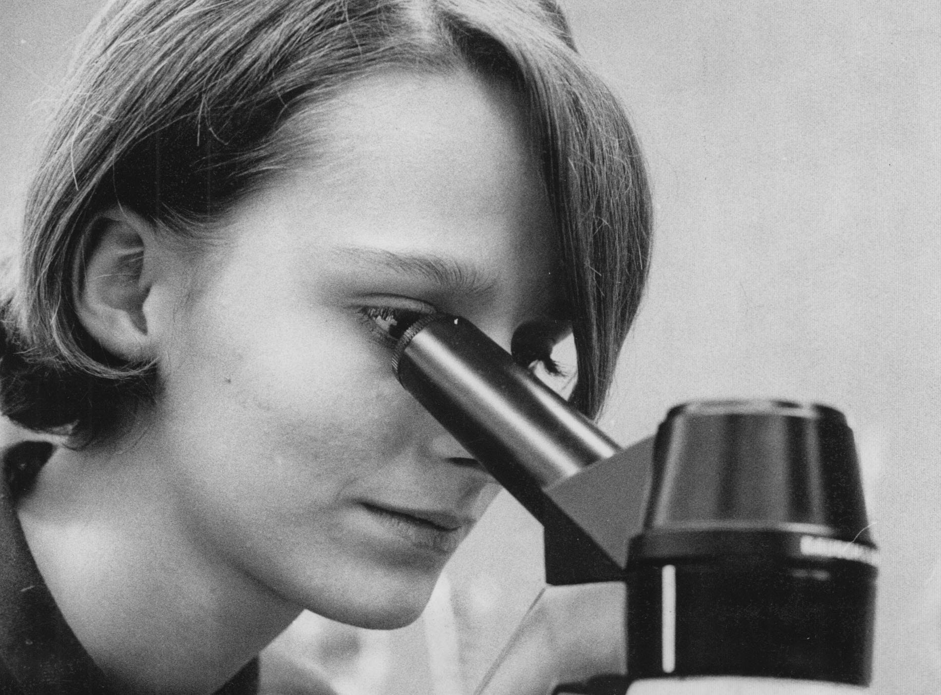 Marshall student, Lou Ann Roemer, examines a slide under a microscope in a science class in 1967.
