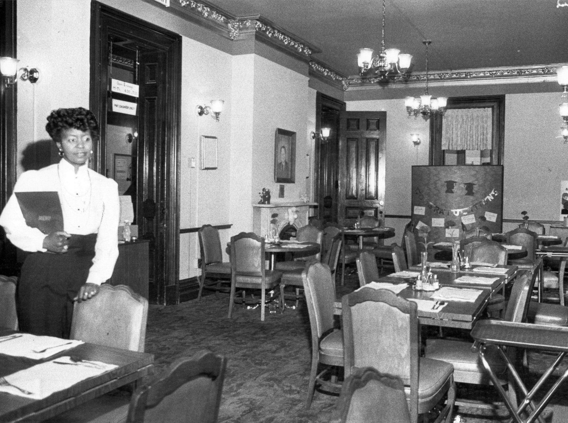 Dorris Raines checks over the Victorian dinning room known as Colonel's Cupboard, a model restaurant on the grounds of Arsenal Technical High School in 1983.