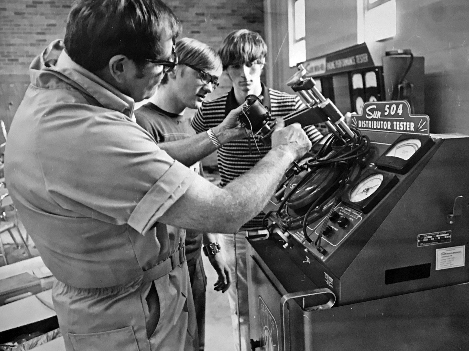 Paul Fiorentin and Paul Stanifer, juniors at Northwest High School listen to teacher Shelby McQueary explain the proper use of a new automotive distributor tester in 1975