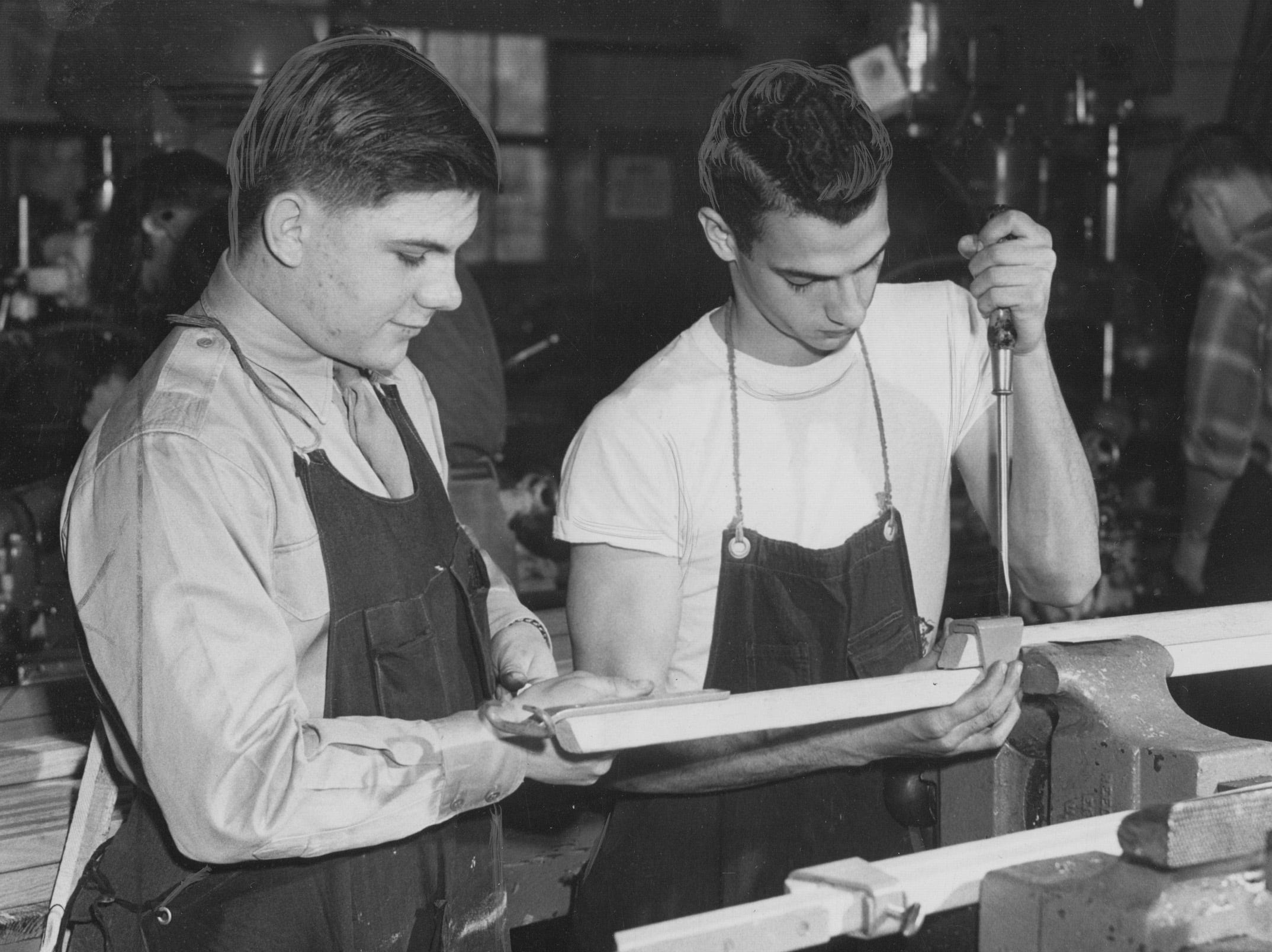 Richard Horner (left) and Floyd Wiggs work in the wood and machine shop at George Washington high School on new stage braces in 1955.