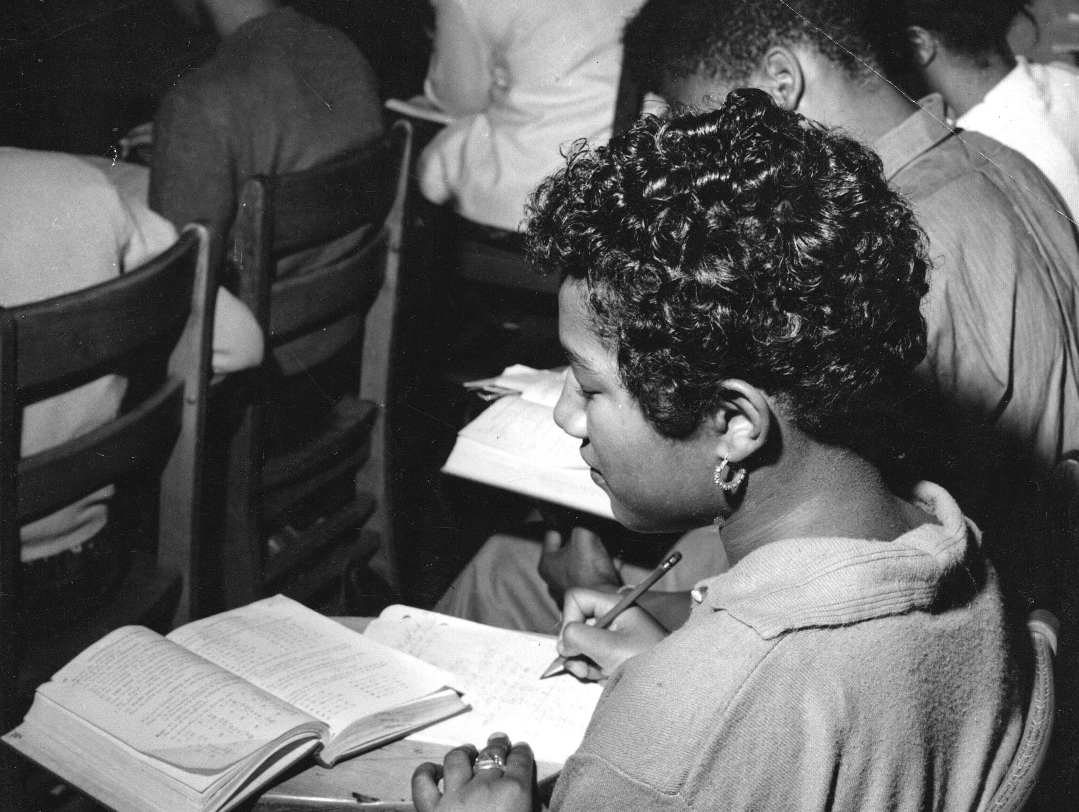 An unidentified Crispus Attucks student works on a math problem in class in 1954.