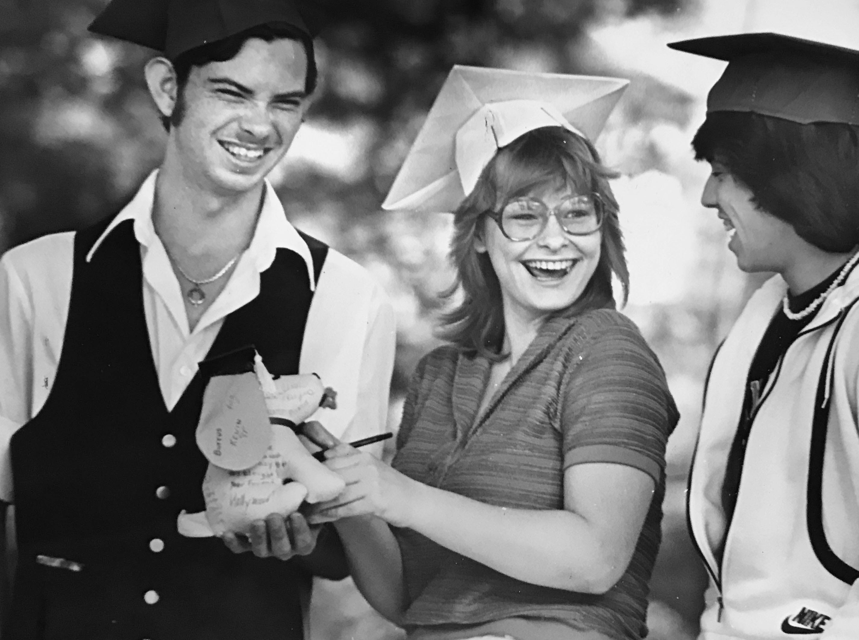 Mark Harmon, Theresa New and Doug Bunten (l to r) seniors at Arsenal Tech High School, sign an autograph dog as they wear their mortar boards for the 1981 graduation.