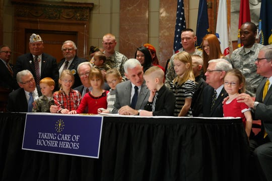 Gov. Mike Pence signs SEA 352, a bill that expands access to the Military Family Relief Fund, on March 13, 2014. Sen. Allen Paul, who carried the legislation, watches.