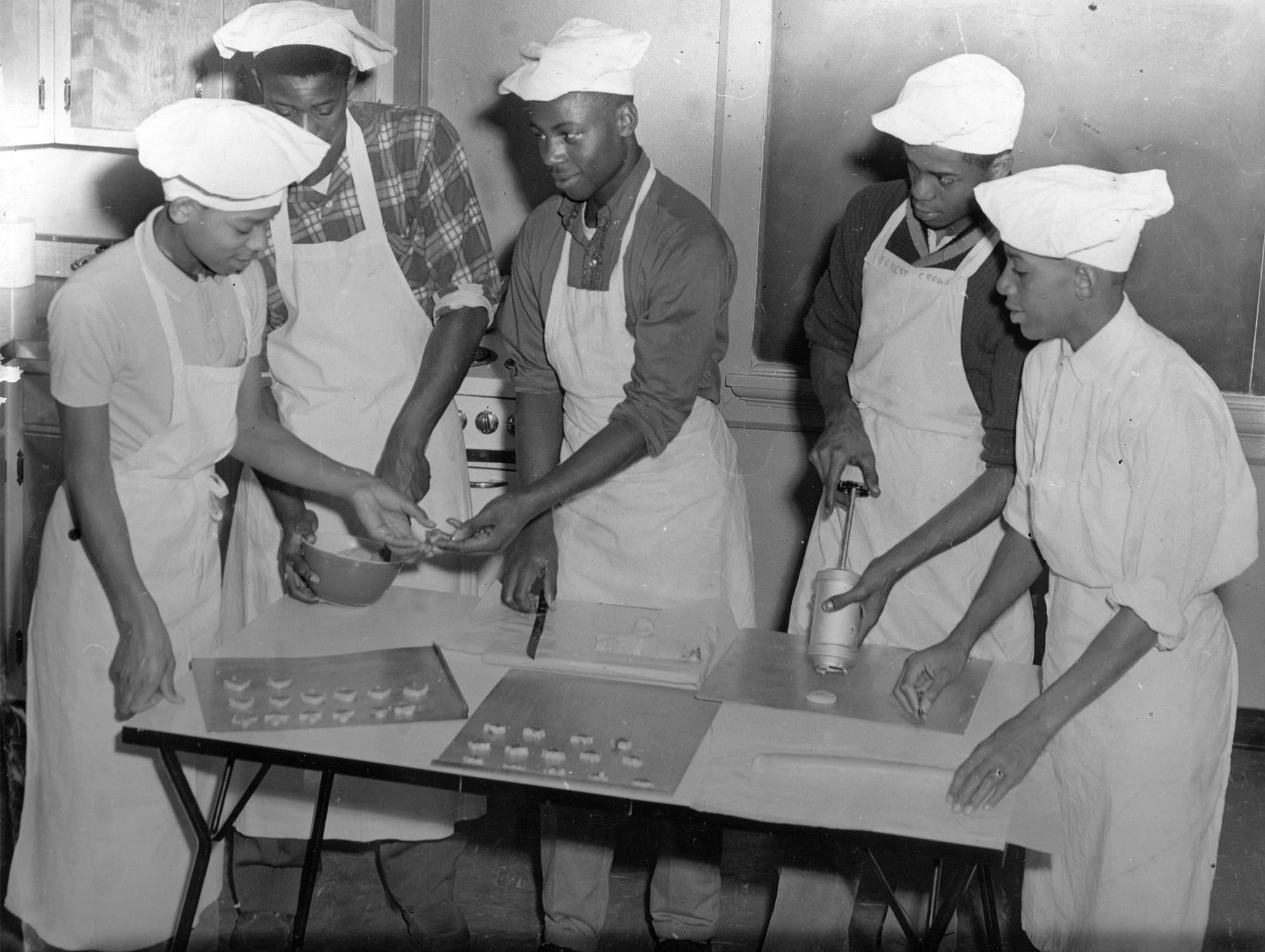 Three hundred dozen cookies were baked by members of Crispus Attucks High School's food-handling class to be distributed to hospitals at Christmas in 1960. The school's Junior Red Cross and home economics department sponsored the Christmas project. Preparing Christmas bell and tree-shaped cookies were (from left): Robert Sharp, Carl Middlebrook, Henry Green, Karl Brady and Edward Torrence. Food classes taught both young men and women how to cook and were considered a significant part of the curriculum.