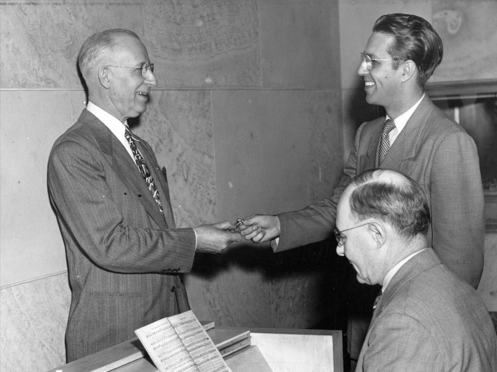 The Arsenal Tech Alumni Association presented the high school with a memorial carillon in memory of graduates killed in World War II in 1947Indianapolis Star . Carl Brandt (left) chairman of the board's building and grounds committee receives the keys to the carillon from William Moon, association president and Frederic Barker, Tech music teacher at the keyboards.