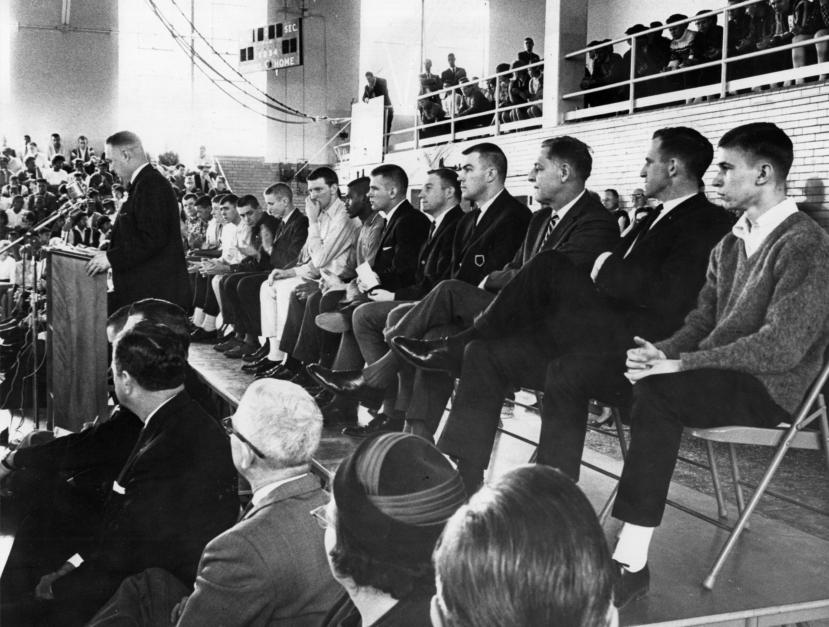 Teacher James Otto addresses the George Washington High School student body as the 1965 Indiana high school basketball state champion Continentals team sits behind him. March 22, 1965.
