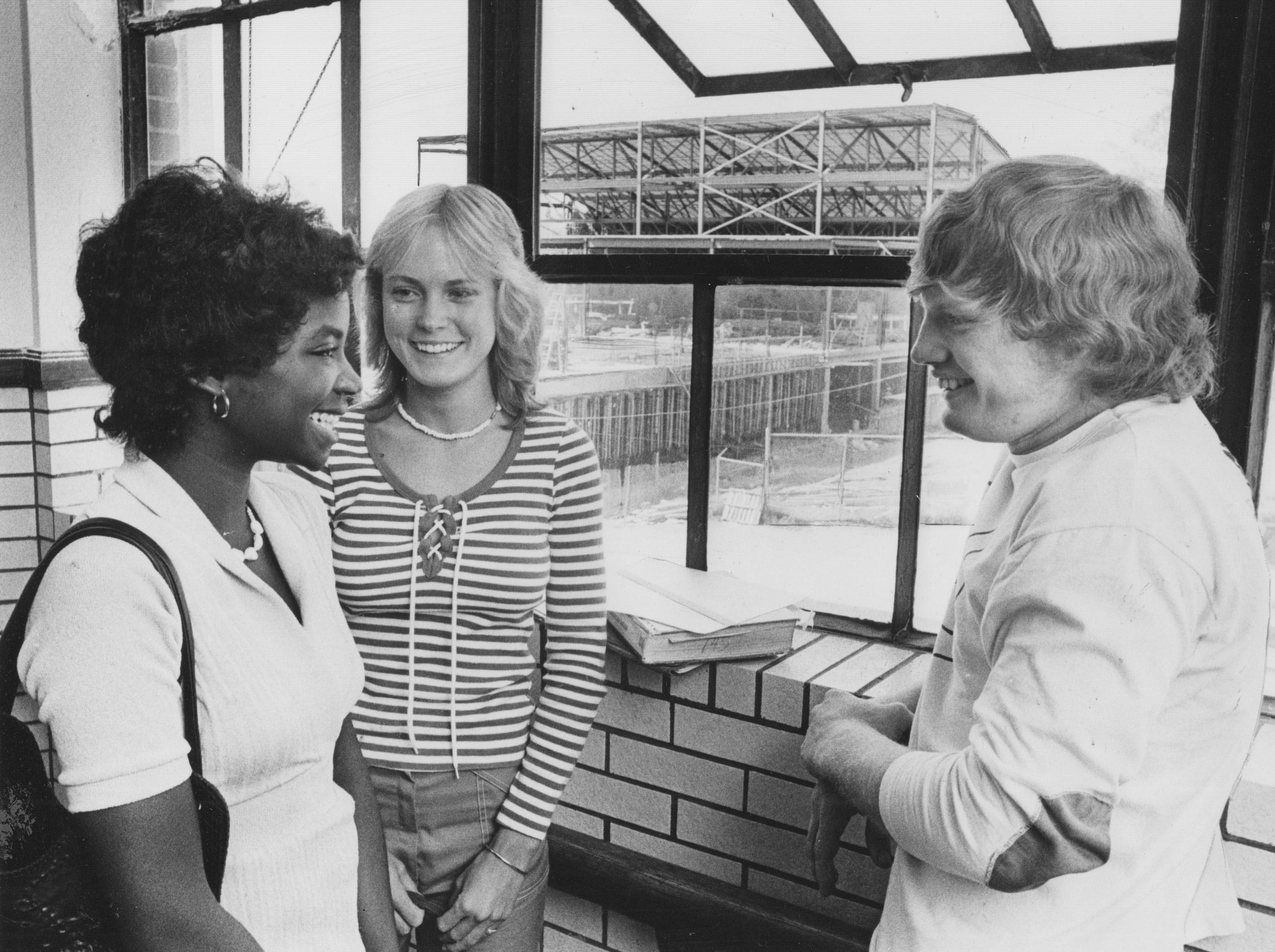 Washington High School students Rhonda Quarles (left) chats with Amy Black and her brother Jeff as construction of a new gymnasium goes on in the back fround in 1975.