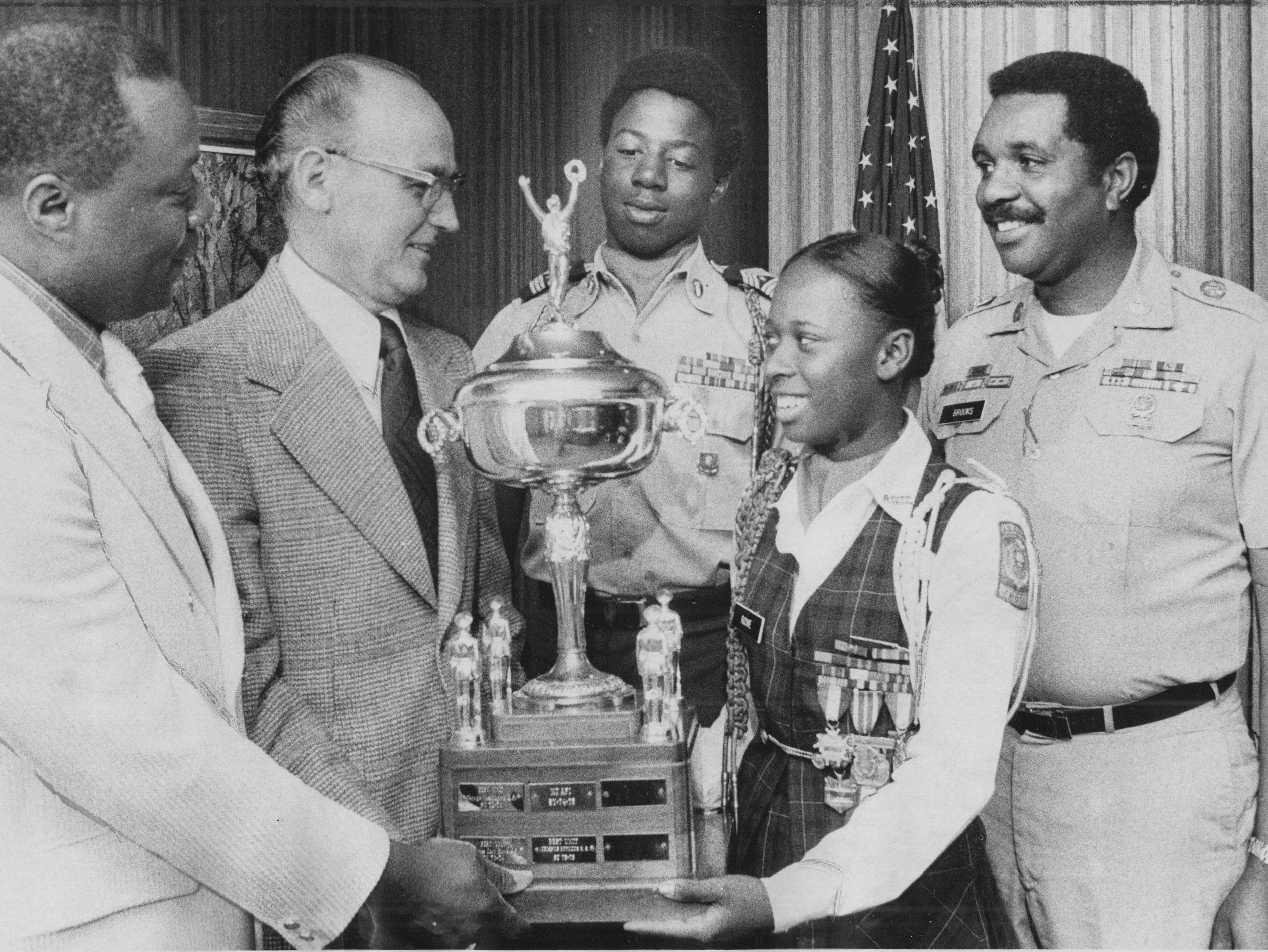 Crispus Attucks High School Junior ROTC unit was honored in 1976 by the Indiana National Guard as the top unit in the state. Shown with the trophy are 9l to r) Earl Donalson, Attucks principal, Indianapolis Schools superintendent Karl Kalp, Cadet Sgt. Maj. Bobby Mills, Cadet Col. Linda Rowe and JROTC instructor M. Sgt. Clarence Brooks.