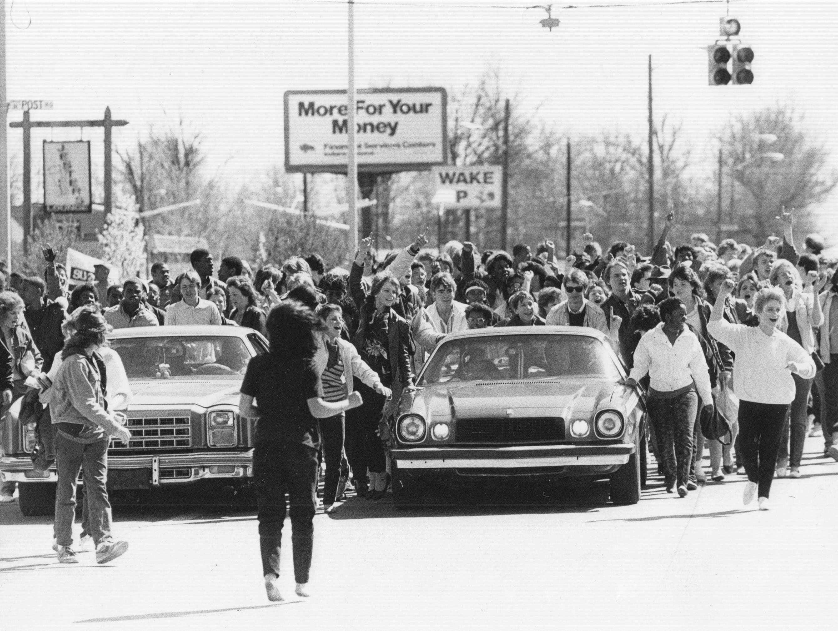 John Marshall High School students cross Post Road at 38th Street en route to the Education Center to protest changing the school to a junior high school in 1986.