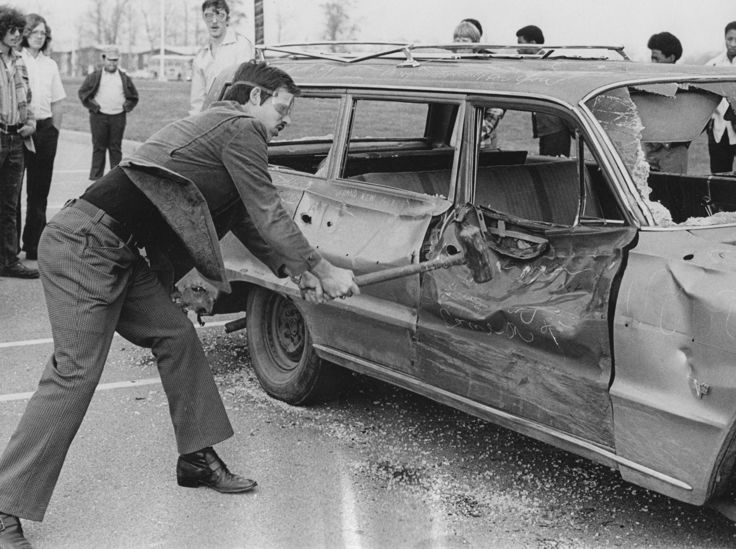 A Marshall High School student takes a swing at an old station wagon with a sledge hammer on the schools outdoor basketball court. Students demolished the car to raise money for a special activities bus for the school.