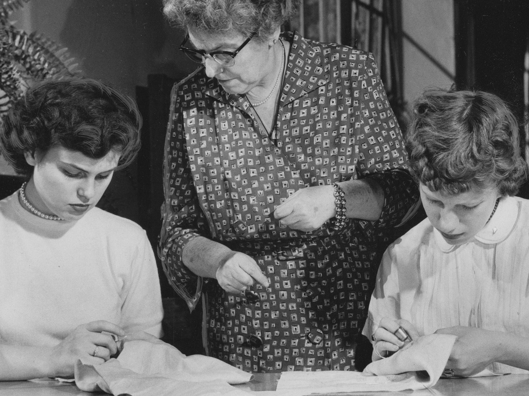 Teacher Margaret Simonds keeps an eye on the stitch work of Joyce Moran (left) and Barbara Griswold in the hand-sewing class at George washington High School in 1955.